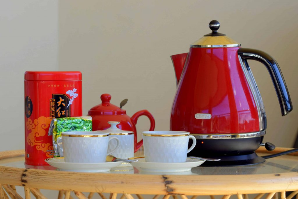 Picture of a red teapot beside white teacups
