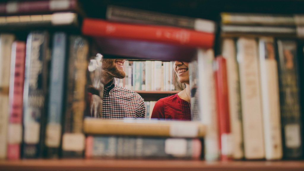 Two people smile while standing near a shelf full of books for our language spotlight.